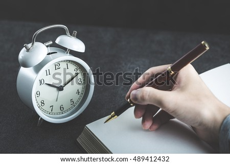 alarm clock and hand writing in notebook