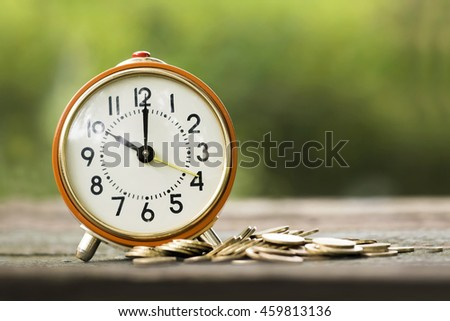 Alarm clock and money coins - time is money concept - stock photo