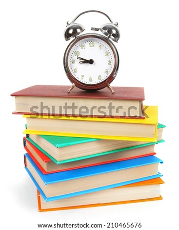Alarm clock and multi-coloured books. On a white background. - stock photo