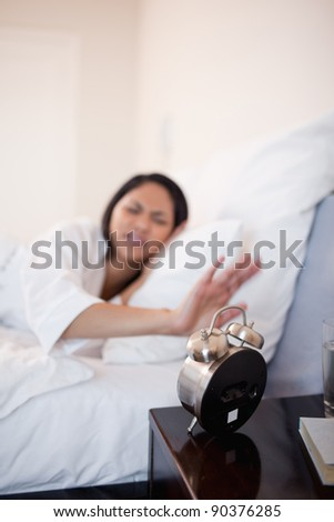 Alarm clock being deactivated by young woman