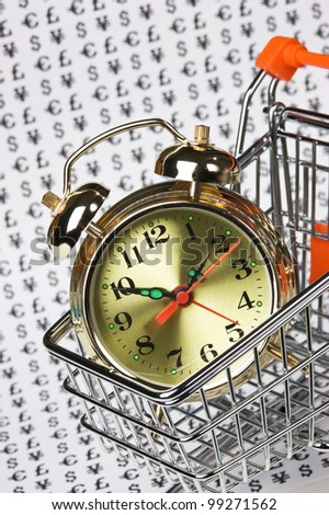 alarm clock in a shopping trolley - stock photo