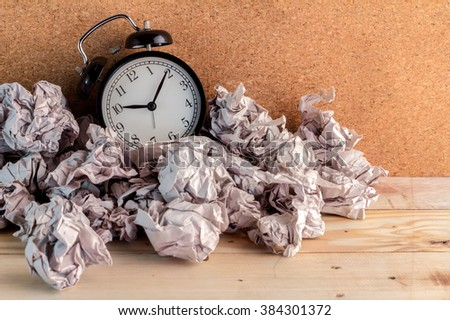Alarm clock in a wastepaper  concept for a time waste of time with cork board texture background - stock photo