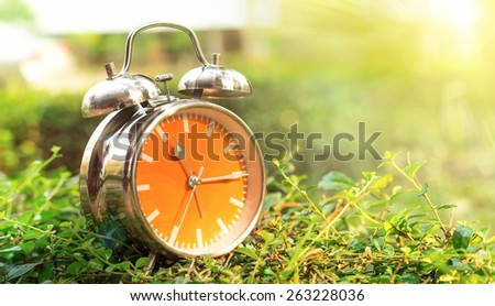 Alarm clock in sunlit on background spring field green and yellow - stock photo