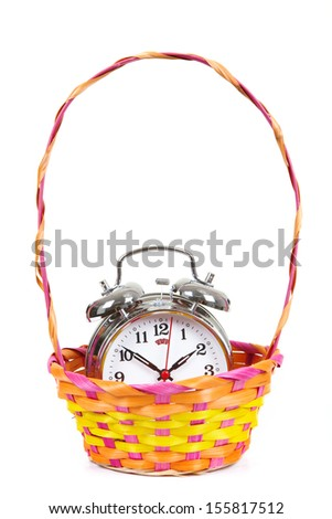 Alarm-clock in the basket on a white background