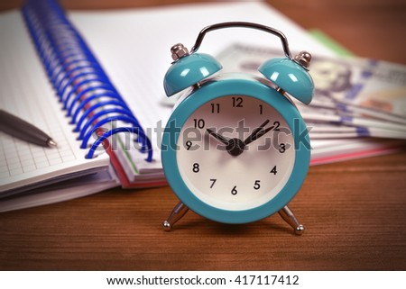 alarm clock, note pad and money on table, close up - stock photo