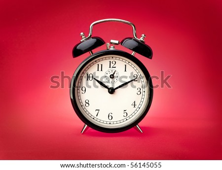 Alarm clock on a red background. Studio shot