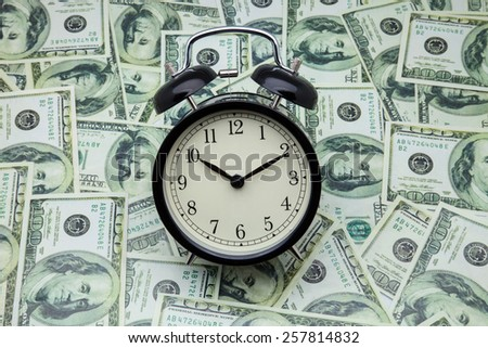 alarm clock on banknotes of one hundred dollars - stock photo