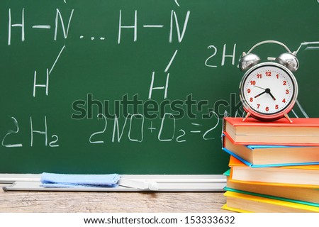 Alarm clock on books. Against a school board with chemical formulas. - stock photo