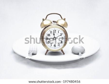 alarm clock on dish (vintage textured style) - stock photo