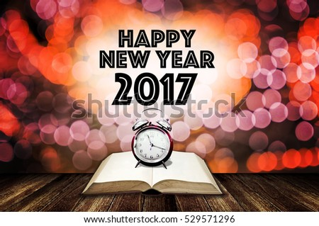 Alarm clock on open book with happy new year greeting word