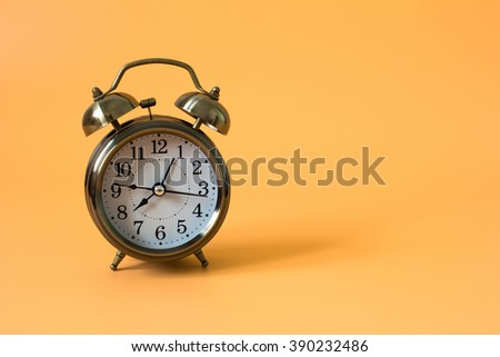 alarm clock on orange background and copy space and write space for write text or message / time concept - stock photo