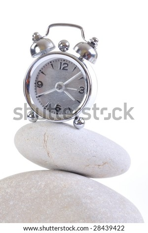 alarm clock on pile of stones - stock photo
