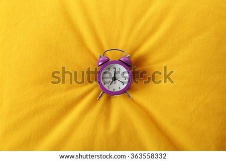 Alarm clock on pillow, close up - stock photo