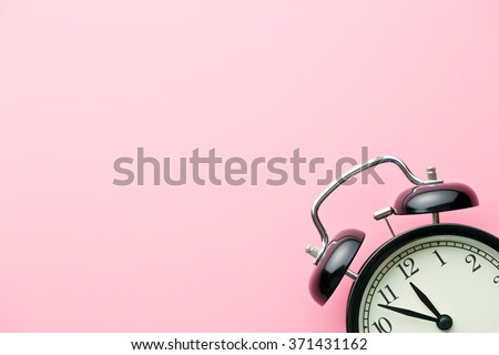alarm clock on pink background - stock photo