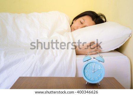 alarm clock on table and woman sleeping in background. (lens blur effect) - stock photo