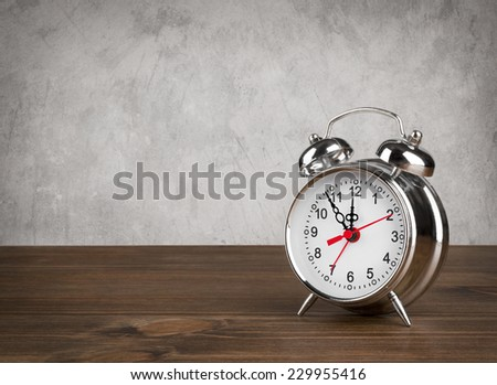 Alarm clock on table over vintage background - stock photo