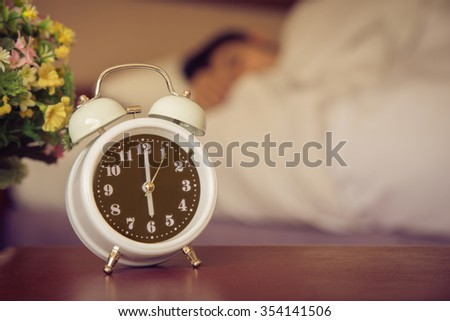 alarm clock on the bed in bedroom. - stock photo