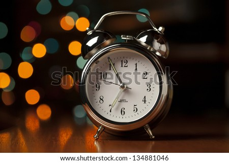 Alarm Clock on the wooden table against unfocused background - stock photo