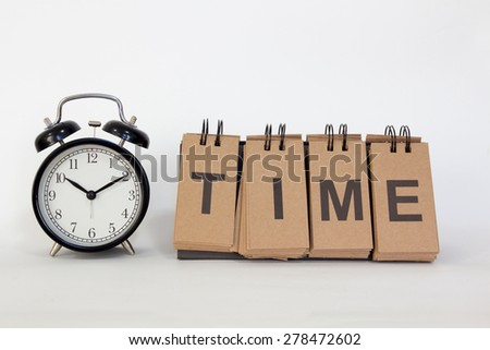 """Alarm clock on white background with wording """"TIME"""" - stock photo"""