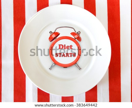 Alarm clock on white plate.Diet start time conceptual icon symbol. - stock photo