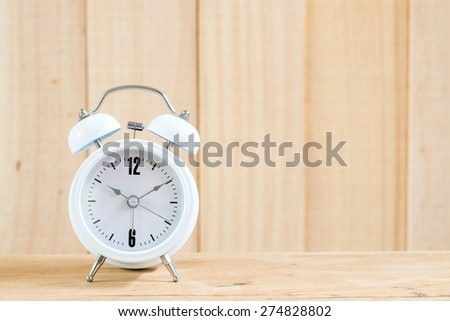Alarm clock on wood background. - stock photo