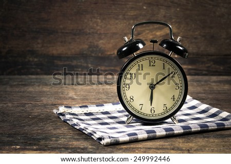 alarm clock on wood table. - stock photo