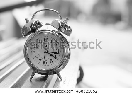 alarm clock on wooden bench in the park, black and white style.