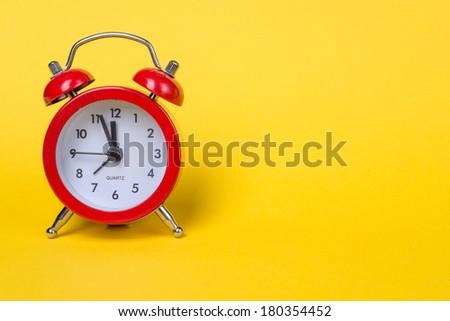 Alarm-clock on yellow background - stock photo