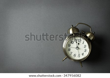 Alarm clock showing almost 12 o clock, with copy space - stock photo