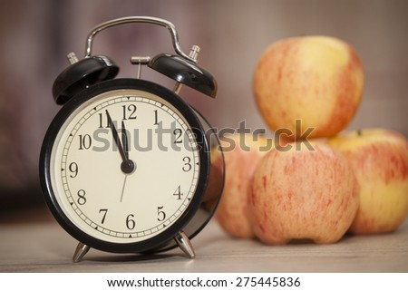 alarm clock showing almost twelve with red and yellow apples blurred on the background. closeup - stock photo