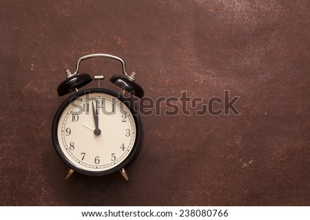 alarm clock showing five mintes to twelve on the brown vintage background - stock photo