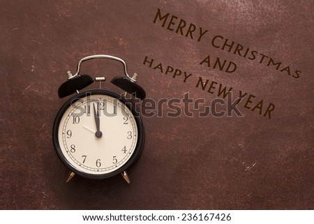 alarm clock showing five mintes to twelve with sign wishing merry christmas and happy new year on the brown vintage background - stock photo