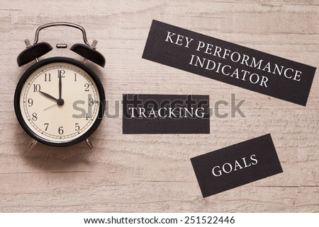 "alarm clock showing ten and signs saying ""key performance indicator, tracking and goals"" on the wooden background - stock photo"