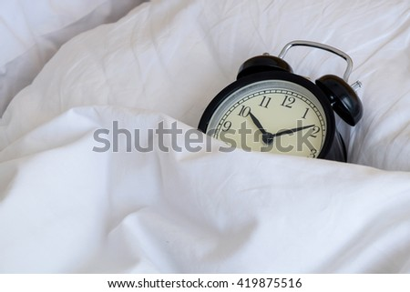 Alarm clock sleeping on the bed in morning