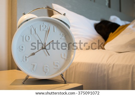 Alarm clock standing on bedside table going to ring early morning to wake up woman in bed sleeping in background.