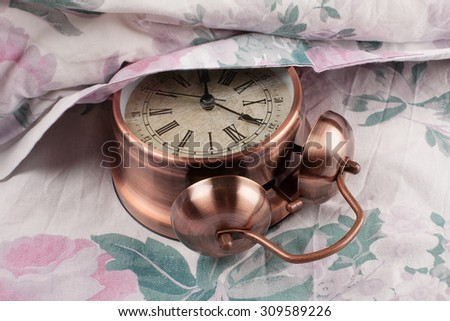 Alarm clock under my pillow - stock photo