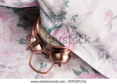 Alarm clock under my pillow - stock photo