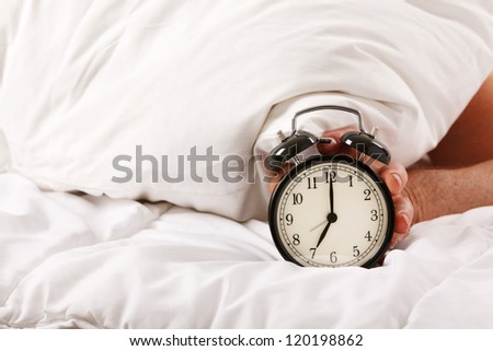 Alarm clock with a sleeping man under cushion