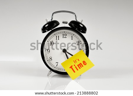 Alarm clock with a yellow note saying it's time - stock photo