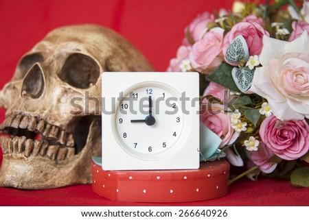 alarm clock with cranium and flowers - stock photo