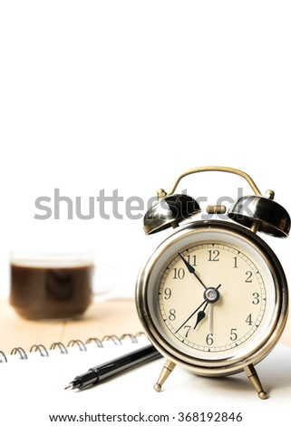 Alarm clock with cup of coffee and white background, selective focus - stock photo