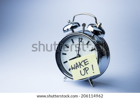 Alarm clock with sticky paper note WAKE UP on white background - stock photo