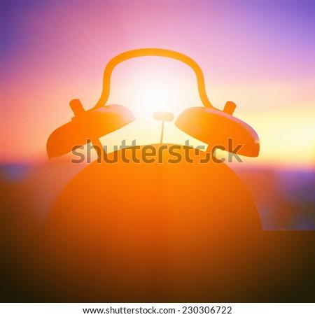alarmclock silhouette at sunrise cityscape - stock photo