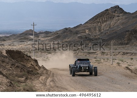 ALASHAN, CHINA-JULY 21, 2016: Sports car gets over the difficult part of the route during the Silk Way rally Moscow-Beijing Dakar series in the rocky desert