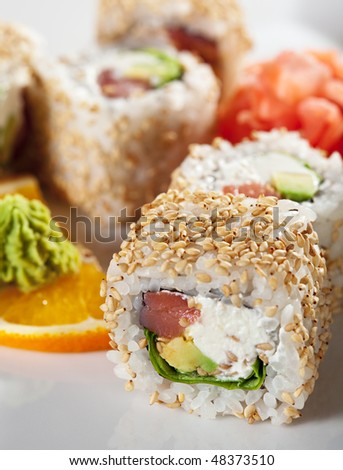 Alaska Maki Sushi - Roll with Smoked Salmon, Cream Cheese, Salad Leaf and Avocado inside. Sesame outside - stock photo