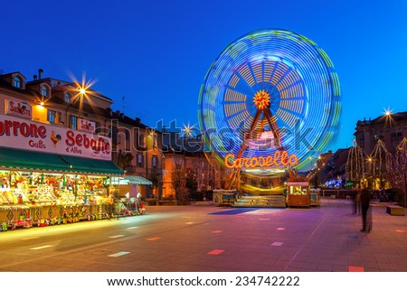 ALBA, ITALY - DECEMBER 30, 2013: Illuminated observation wheel and stall with sweets on town square as part of traditional Christmas and New Year celebrations. - stock photo