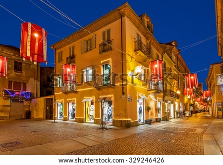 ALBA, ITALY - DECEMBER 30, 2014: Pedestrian street with shops in old town illuminated for Christmas celebrations. This area is very popular with locals and tourists visiting Alba for winter holidays. - stock photo