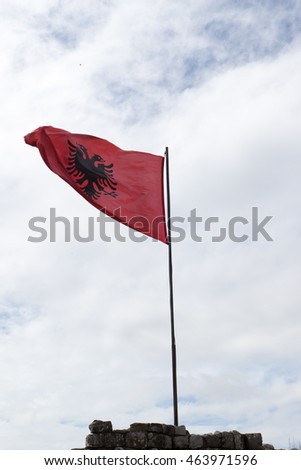 Albania flag against blue sky with clouds