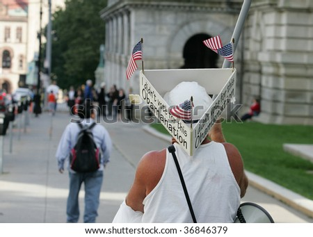 ALBANY, NY- SEPT 10: A Protester wears signs against President Obama's policies during a stop of the Tea Party Express tour on Septemmber 10, 2009 in Albany NY - stock photo