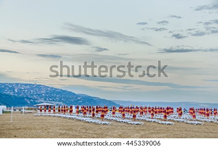 ALBENA, BULGARIA - JUNE 13, 2016. View of the Black Sea shore, green hills with houses, blue clear water, clouds sunset sky, beach sand with umbrellas and sunbeds. City Balchik coast.